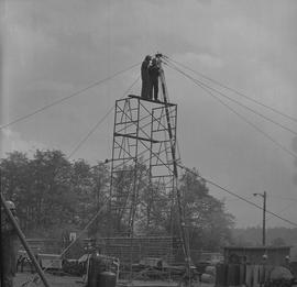 Structural steel, 1971; two men standing at the top of scaffolding holding onto a tall pole
