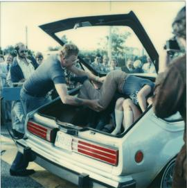 Student Rally 1984 ; students in the trunk of a car ; man helping a student fit into the trunk