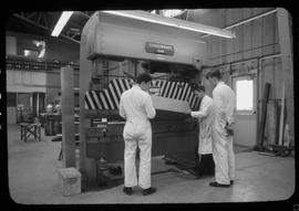 Sheet metal, 1968; instructor and two students using a large machine to cut sheet metal