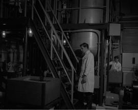 Forest Products, 1966; a man in a lab coat standing at the bottom of a stair case in a forest pro...