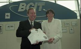 BCIT open house '98, First Nations woman presenting a clothing item to a man [5 of 6 photographs]