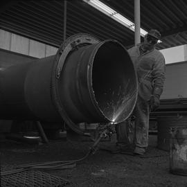 Welding, Nanaimo, 1968; man wearing protective goggles rotating a pipe that is being welded [2 of 2]