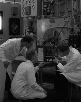 Mechanical technology, 1967; three men using a machine for gas analysis on a steam boiler