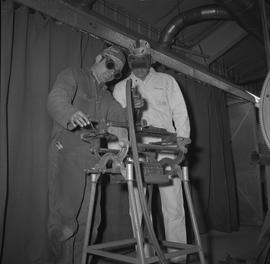 Welding, Terrace, 1968; two men wearing protective goggles looking at a piece of welding equipment