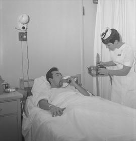Nursing, 1968; a nurse attending to a patient checking respiration and adjusting a respiration me...