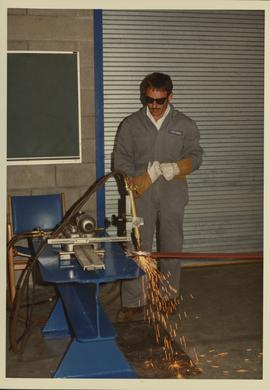 Man with welding equipment; Welding building opening May 1983