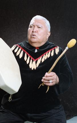 Bob George, First Nations elder, in First Nations garment playing an instrument [26 of 36 photogr...