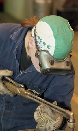 Trades discovery for women; steel fabrication, students wearing protective gear while using steel...