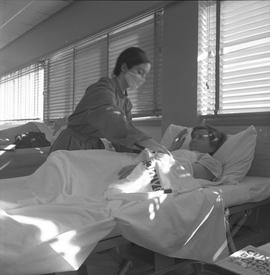 Practical nursing, Prince George, 1968; nurse wearing a face mask attending to a patient [1 of 3]