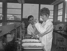 Food Processing Technology, 1966; woman in a lab coat holding a spoon with food ; man in a lab co...