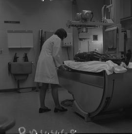 Medical radiography, 1968; woman in a lab coat preparing to x-ray a manikin