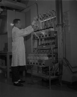 Food Processing Technology, 1966; man wearing a lab coat performing food processing tests