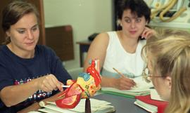 C/Care (students in action), 1993, students with model of a human heart [2 of 3 photographs]