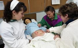 General Nursing, students and nurse examining dummy patient in a bed [4 of 5 photographs]