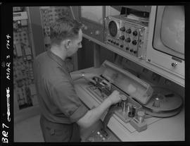 Man working at tape reel station [2 of 2 photographs]