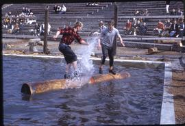 Lumberjack event; two men competing in a logrolling competition, audience in background