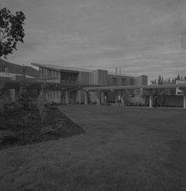Terrace campus, BCVS, 1971; people walking under covered walkway, garden and lawn area, buildings