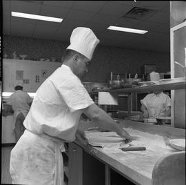 BC Vocational School Cook Training Course ; student preparing a pie crust ; students in background