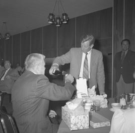 Roy Brown retirement party; Roy Brown holding up a cup and a man pouring a drink; people in backg...
