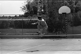 BCIT image of a man leaping over the net on a BCIT Tennis court.