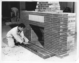 Bricklaying; A student checking the level of the hearth of a brick fireplace, another student wor...