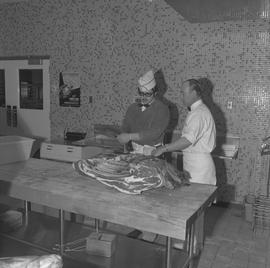 Meat cutting, 1968;  a student cutting a large piece of meat with a saw and the instructor watching