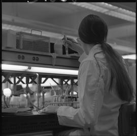 Medical laboratory technology, 1968; student in lab coat examining contents of a test tube [2 of 2]