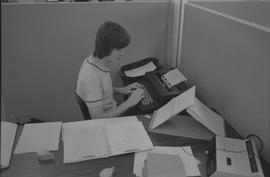 Pacific Vocational Institution ; a student using a typewriter and looking a typewriting exercise ...