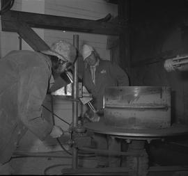 Welding, Prince George, 1968; instructor watching a man wearing protective goggles using a piece ...