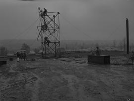 Structural steel, 1968; students constructing a steel structure in a muddy field