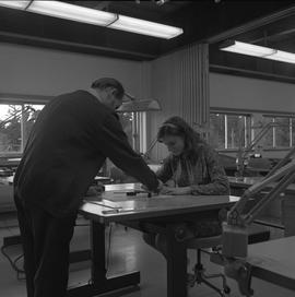 Map drafting, Victoria, 1968; instructor working with a female student on a map drawing