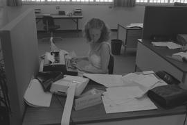 Pacific Vocational Institution ; student using a typewriter and reading papers on the desk
