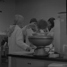 Medical laboratory technology, 1968; four women in lab coats studying contents of two test tubes ...