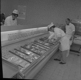 Meat cutting, 1968;  a man picking up packed meat from a cooler and a man watching ; man working ...