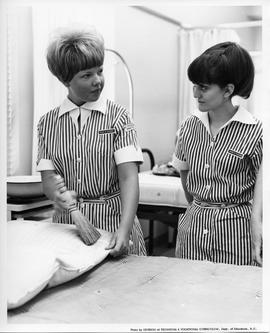 Miss J. Cloues and Miss F. Palmer, BCVS Practical Nursing students, with hand broom beside bed, 1967