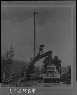 Logging, 1968; copy negative; picture of a log loader moving logs onto a truck bed and a tower ya...
