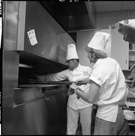 BC Vocational School Cook Training Course ; student using a peel to remove food from an oven ; in...