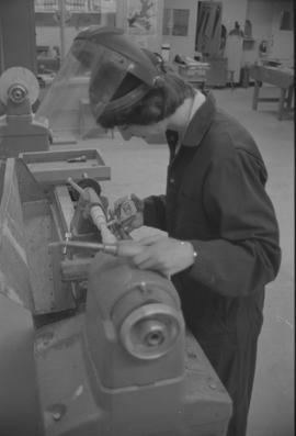 Pacific Vocational Institution ; carpentry student measuring wood on a wood lathe