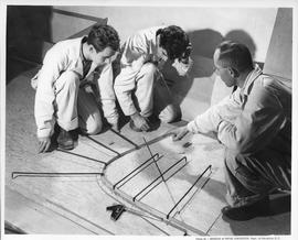 Three men kneeling down and measuring wood for boat building; Photo by the Division of Visual Edu...