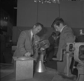 Sheet metal, 1968; instructor demonstrating to a student how to use a tool to round edges on a cy...
