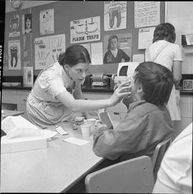 BC Vocational School Dental Assistant program ; a student examining a child's teeth
