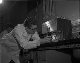 Gas and Oil, 1966; man in a lab coat holding a stop watch and testing liquid using Labline testin...