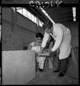 B.C. Vocational School; Carpentry Trades instructor demonstrating the use of carpentry equipment ...