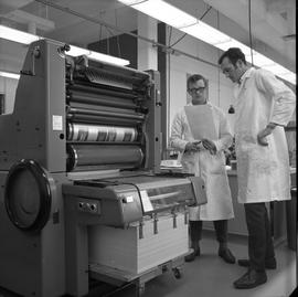 BCVS Graphic arts ; two men standing next to printing equipment and looking at paper