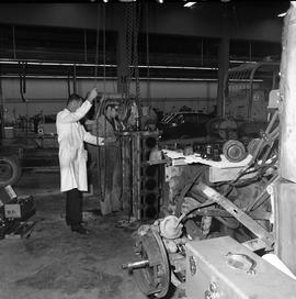 BCVS Heavy duty mechanic program ; an instructor and two students lifting an engine using a pulley
