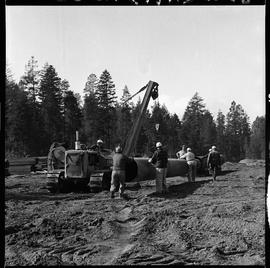 Heavy duty equipment operator, Nanaimo ; group of men help a man operating a Caterpillar pipelayer