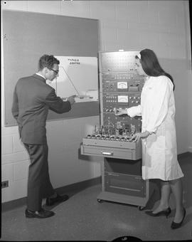 BCVS Health Data Processing ; woman adjusting settings of an analog computer ; man pointing at gr...