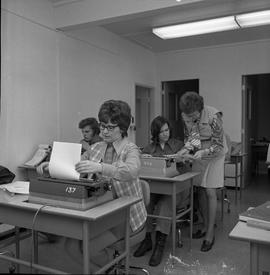 BC Vocational School Commercial Program; students typing ; instructor checking a student's work