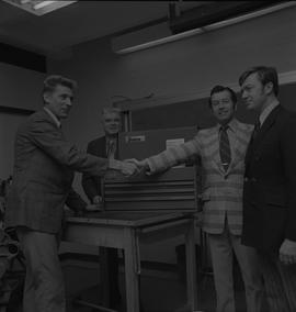 Tool box presentation; two men shaking hands, two men watching