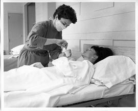 BCVS Nursing student, wearing mask, holding cup near patient (ca. 1968)